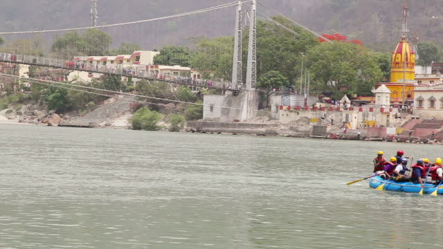 ws pan view of people rafting in ganges river / rishikesh, uttarakhand, india - 史跡めぐり点の映像素材/bロール