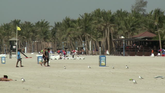 WS PAN View of people relaxing on beach / Dubai, United Arab Emirates