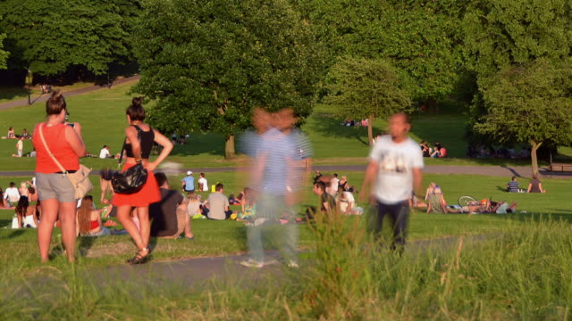 MS T/L View of people relaxing on grass and move on pathway at Primrose Hill / London, Greater London, United Kingdom