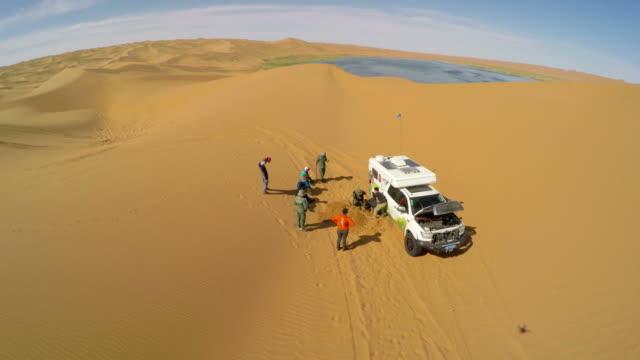 ws aerial view of people repairing car in tengger desert/alashan, inner mongolia, china. - 修理する点の映像素材/bロール
