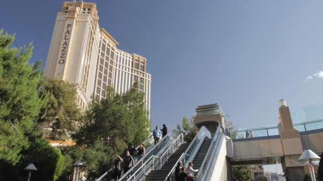 view of people riding escalator near palazzo hotel and casino on the strip, las vegas boulevard, las vegas, nevada, usa - the palazzo las vegas stock videos & royalty-free footage