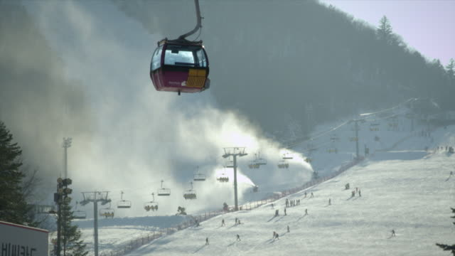 view of people riding snow board and ski on a snowfield and overhead cable car at ski resort in pyeongchang (2018 winter olympics) - seggiovia video stock e b–roll