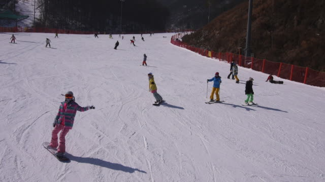 View of people riding snow board and ski on a snowfield at ski resort