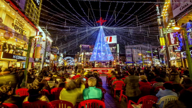 ws t/l view of people sitting on chair to see performance in nampodong christmas tree culture festival (popular travel destination) / busan, gyeongsangnam do, south korea  - 座る点の映像素材/bロール