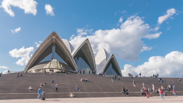 view of people sitting on the stairway of opera house, sydney, australia - ニューサウスウェールズ州点の映像素材/bロール