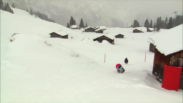 ws view of people sledding in swiss alps / gimmelwald, berner oberland, switzerland - gimmelwald stock videos & royalty-free footage