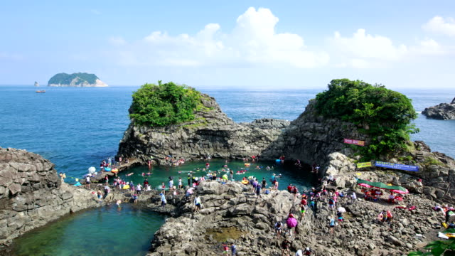 view of people snorkeling in seonnyeotang (natural pool) at hwangwooji beach - cay insel stock-videos und b-roll-filmmaterial