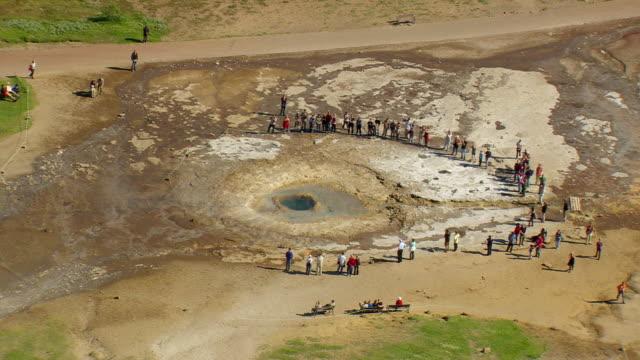 vídeos de stock, filmes e b-roll de ws zo aerial view of people standing near strokkur geyser / iceland - gêiser strokkur