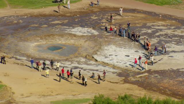 vídeos de stock, filmes e b-roll de ws aerial view of people standing near strokkur geyser / iceland - gêiser strokkur