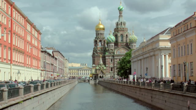 MS PAN View of people walk on pathway next to Winter Canal with Church of Savior on Spilled Blood aka Cathedral of Resurrection of Christ and stormy clouds overhead / St. Petersburg, Russia