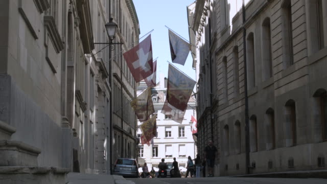 WS LA View of people walkinf on street and cyclists passing with flags frame corridor / Geneva, Switzerland