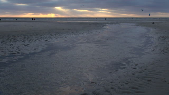 vídeos de stock, filmes e b-roll de ews view of people walking and playing with beach kites in sea ebb tide during sunset , north sea north frisia, / st. peter ording, schleswig holstein, germany - vazante