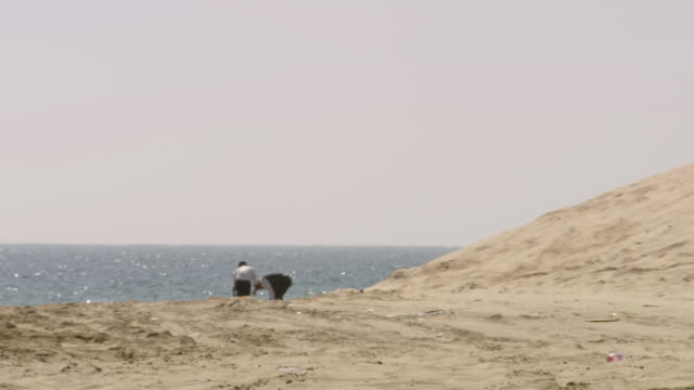 ws pan view of people walking around on the beach / doha, qatar  - qatar stock videos & royalty-free footage
