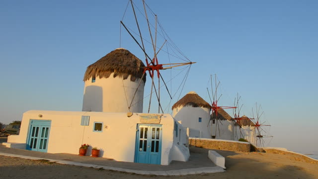 stockvideo's en b-roll-footage met ws view of people walking by famous five old 14th century windmills of white at sunset / mykonos, greece - vijf dingen