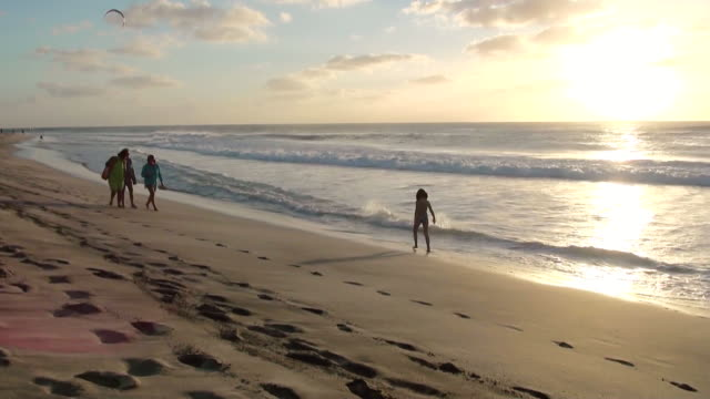 ms view of people walking on beach near santa maria / santa maria, sal, cape verde - 数人点の映像素材/bロール