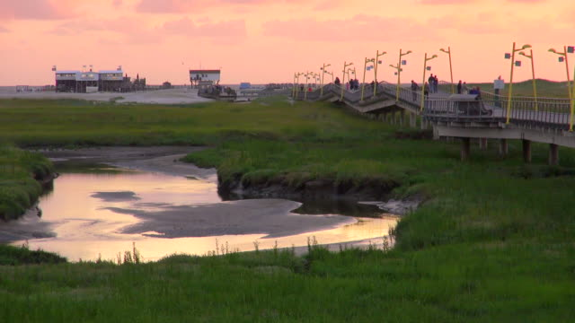WS View of people walking on bridge at resort during sunset, North Sea North Frisia, / St. Peter Ording, Schleswig Holstein, Germany