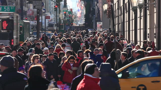 ws view of people walking on crowd sidewalk at fifth avenue in christmas seasons smoke blowing from street vender which surrounds people with traffic congestion / new york, united states - 目抜き通り点の映像素材/bロール