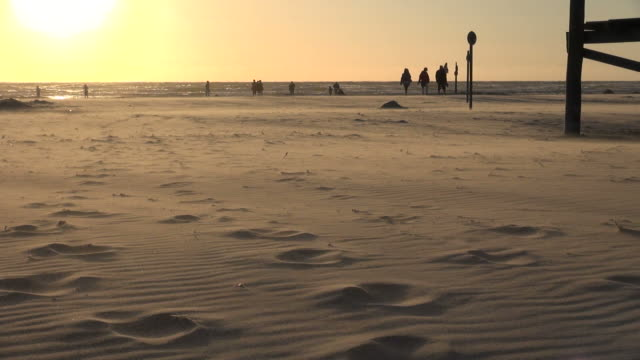 ws view of people walking on sea coast and sea sand flying by wind during sunset, north sea north frisia, / st. peter ording, schleswig holstein, germany - north sea stock videos & royalty-free footage