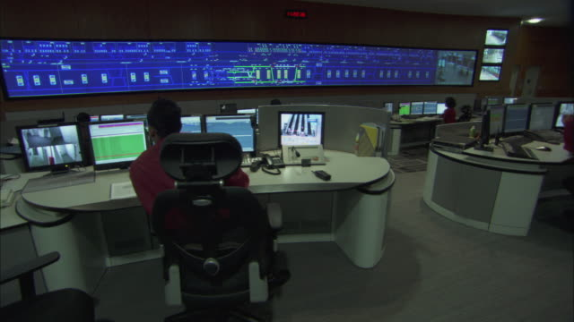 MS PAN View of people working at workstations and large surveillance monitor mounted on wall in control room in Singapore