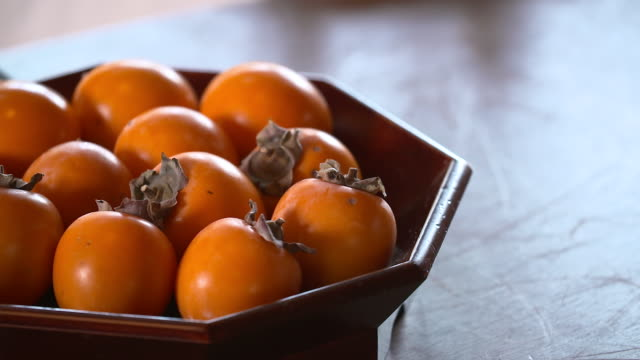 vidéos et rushes de view of persimmon on the bowl - coupe à fruits