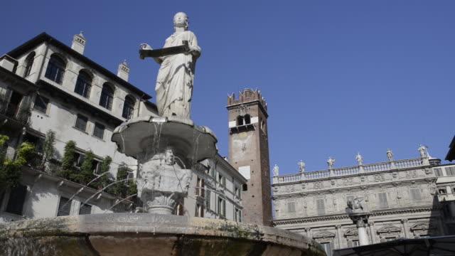 vídeos de stock, filmes e b-roll de ms pan view of piazza delle erbe in front of square with fountain madonna verona / verona, veneto, italy - figura feminina