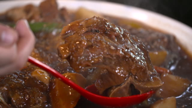 view of picking up back ribs in ppyeo jjim(braised back ribs in south korea) with ladle - ladle stock videos & royalty-free footage