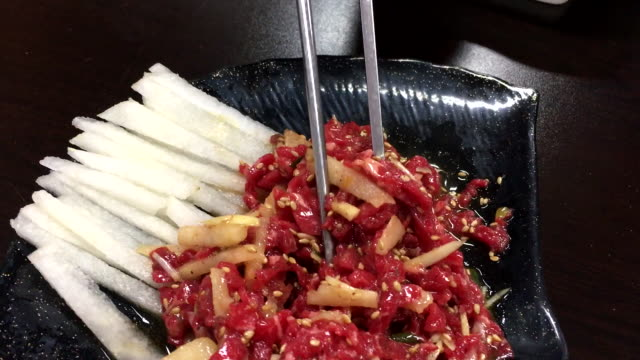 view of picking up beef tartare (korean-style raw beef) - steak tartare stock videos and b-roll footage
