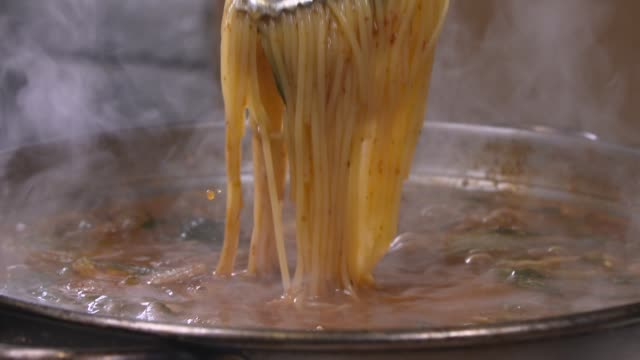 vídeos de stock e filmes b-roll de view of picking up corn noodles with tongs - comida chinesa