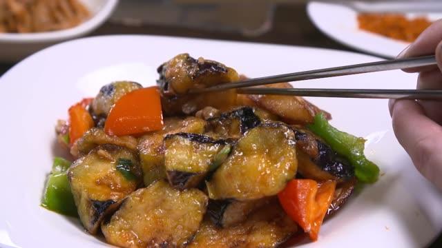 vídeos y material grabado en eventos de stock de view of picking up eggplant with chopsticks in chinese food di san xian(fried potatoes, eggplant and peppers) - freír mediante inmersión total en aceite caliente