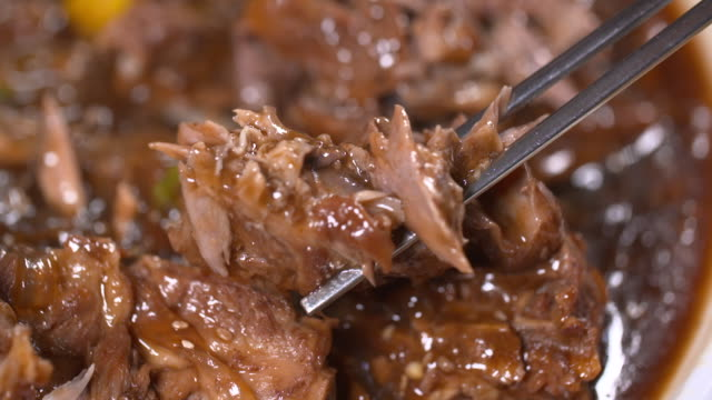 view of picking up ppyeo jjim(braised back ribs in south korea) with chopsticks - braised stock videos and b-roll footage