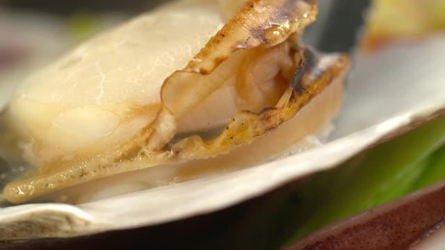 vídeos de stock e filmes b-roll de view of picking up scallop in clam jeongol(clam hot pot in south korea) - concha utensílio de servir