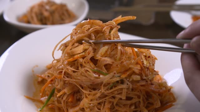 view of picking up tofu noodles with chopsticks - noodles stock videos & royalty-free footage