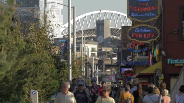 view of piers and people along alaskan way towards centurylink fields, seattle, washington state, united states of america, north america - seattle stock videos & royalty-free footage