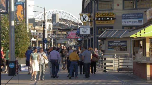 view of piers and people along alaskan way towards centurylink fields, seattle, washington state, united states of america, north america - seattle stock-videos und b-roll-filmmaterial