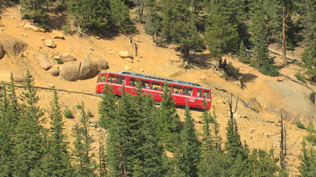 ms ds zo aerial view of pikes peak cog railroad driving up steep incline up mountain and forested mountainside with rocky peak / colorado, united states - steep stock videos & royalty-free footage