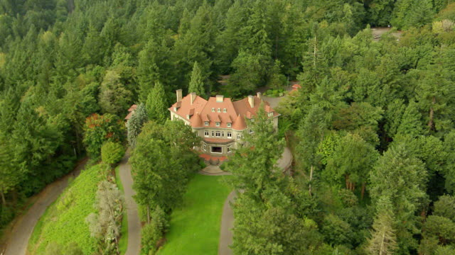 WS AERIAL DS ZI ZO View of Pittock Mansion on hill surrounded by evergreen trees / Portland, Oregon, United States