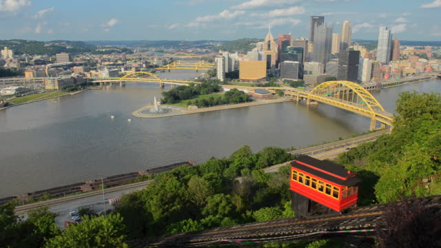 WS View of Pittsburgh Pennsylvania from Mt Washington hill looking at Golden Triangle and city skyscrapers where the three rivers and red incline cars coming up mountain / Pittsburgh, Pennsylvania, United States