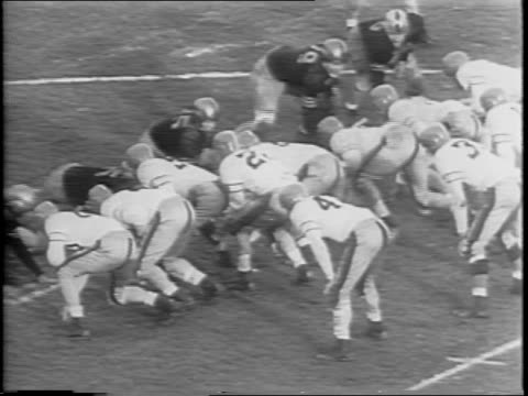 view of players on field as navy player bruce smith intercepts ball / view of sailors and spectators cheering in stands / close up of navy player... - アメフト ファーストダウン点の映像素材/bロール