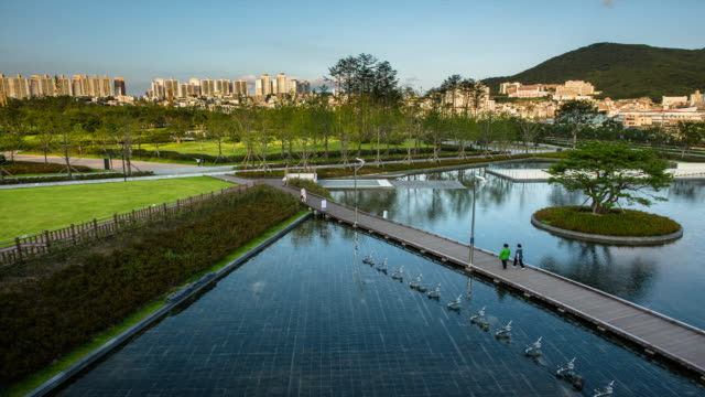view of pond in citizen's park and people walking on the bridge - busan stock videos & royalty-free footage
