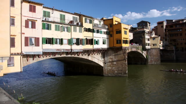 ws view of ponte vecchio bridge and kayak moving near river arno / florence, italy - ponte stock videos & royalty-free footage