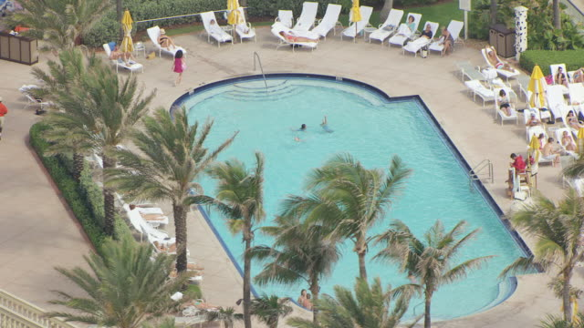 ms aerial zo view of pool with guests swimming and hotel with ocean / palm beach, florida, united states - freibad stock-videos und b-roll-filmmaterial
