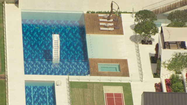MS AERIAL ZO DS View of pools and deck in front of large house / Jupiter, Beach Florida, United States
