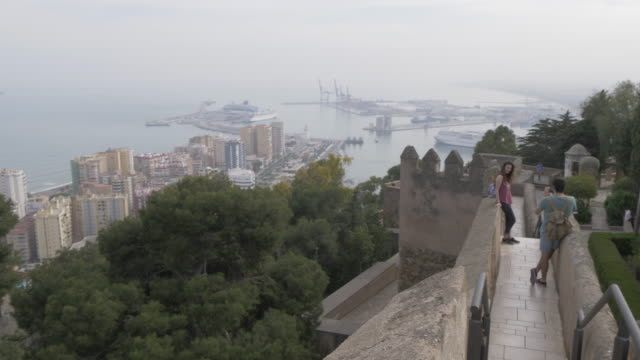 view of port and castle walls from castillo de gibralfaro, malaga, andalucia, spain, europe - andalucia stock videos & royalty-free footage