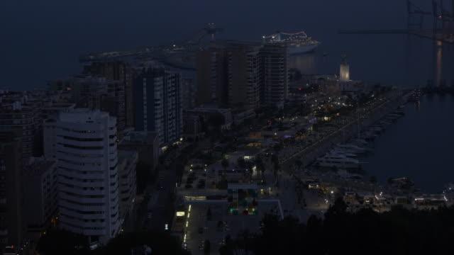 view of port at dusk from castillo de gibralfaro, castle, malaga, andalucia, spain, europe - campo totale video stock e b–roll