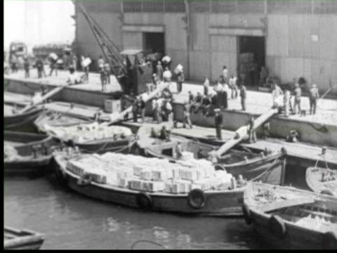 b/w view of port man loading boxes on boat  audio /  palestine - articolo video stock e b–roll