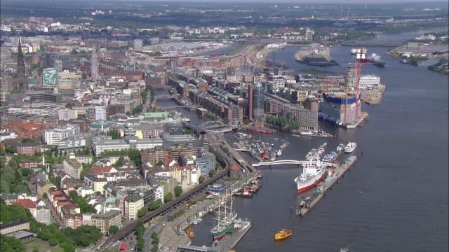 aerial ws view of port nearby city / hamburg, hamburg, germany - porto marittimo video stock e b–roll