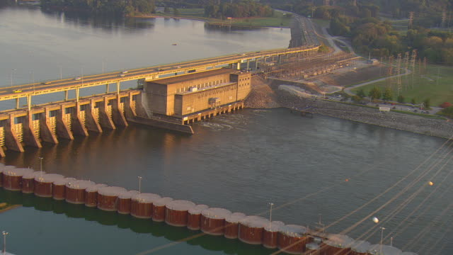 ws aerial view of powerlines to substation at powerhouse of chickamauga dam on tennessee river with traffic crossing dam on highway 153 / chattanooga, tennessee, united states  - dam stock videos and b-roll footage