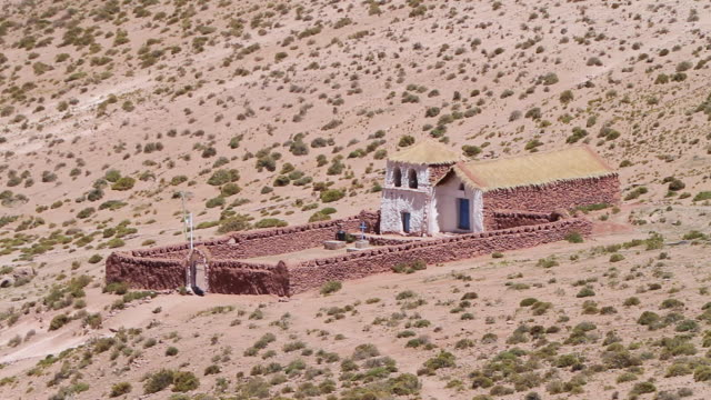 ws view of primitive stone church looking structure with flag blowing in wind thatched roof and white colored front walls in middle of light brown desert with small green shrubs - thatched roof stock videos & royalty-free footage