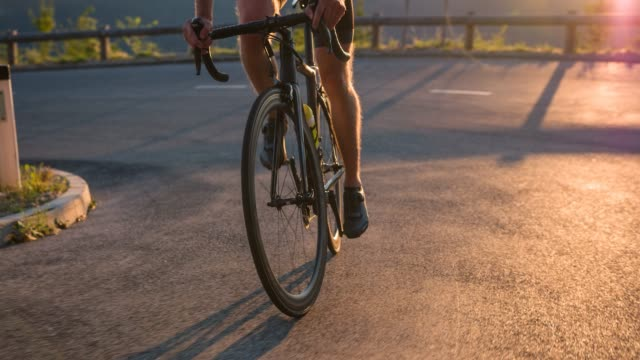view of professional road cyclists legs, pedaling uphill at sunset - racing bicycle stock videos and b-roll footage