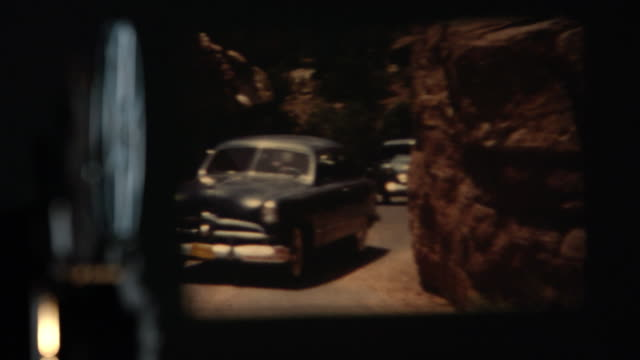 view of projector playing old film of cars driving - proiezione evento pubblicitario video stock e b–roll